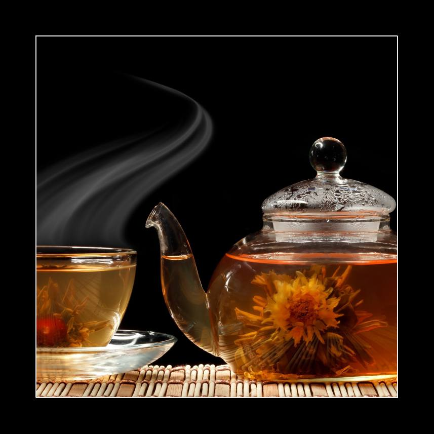 Glass teapot and a cup of green tea on a black background